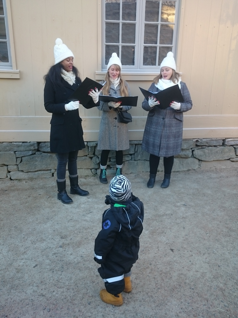 Tre kvinnor i vinterkläder står utomhus och sjunger framför ett barn